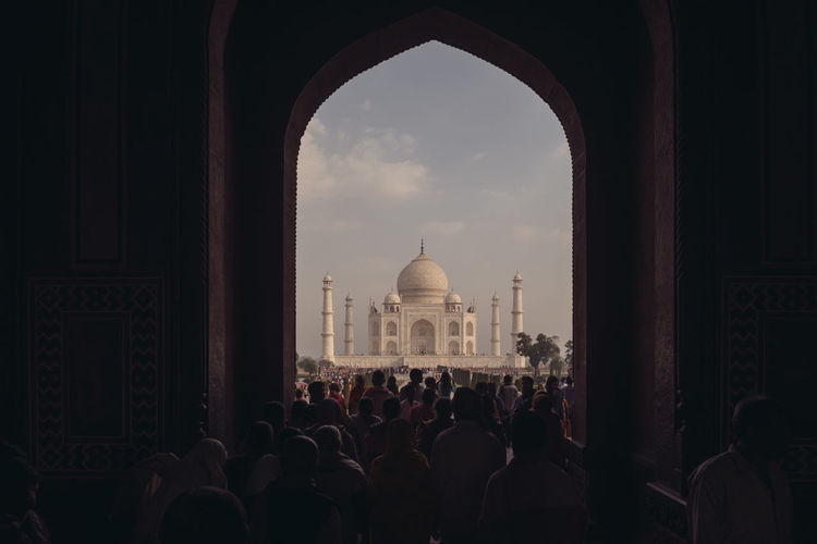 People in front of taj mahal against sky