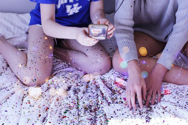 Midsection Of Friends Using Smartphone While Sitting On Bed Covered With Confetti At Home