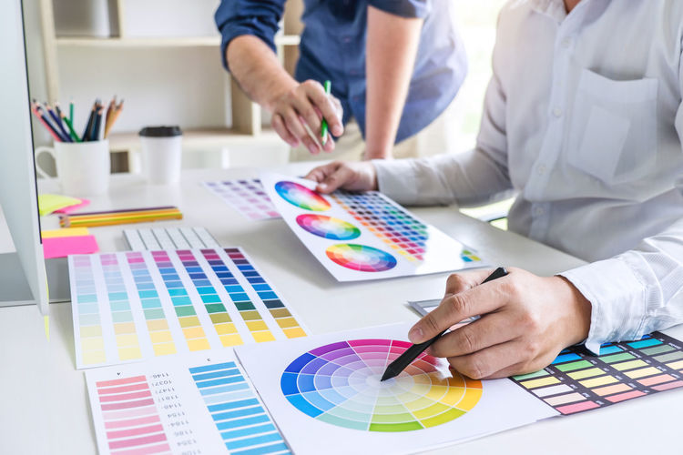 Choosing Adult Art And Craft Business Colleague Color Chart Colored Pencil Colorful Creativity Design Professional Graphic Design Hand Holding Human Hand Indoors  Men Multi Colored Occupation Pantone Paper Pen People Swatch Table Working