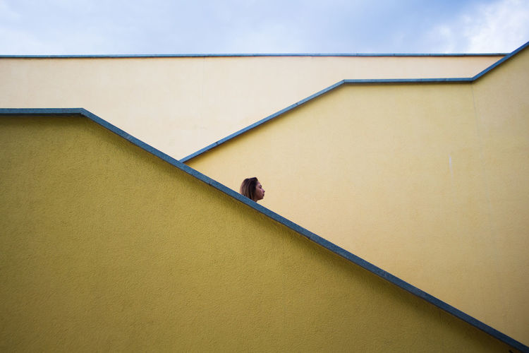 Low angle view of woman against yellow wall of building