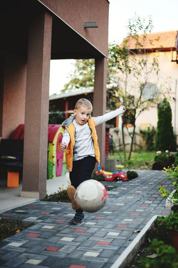 Full length portrait of cute boy kicking ball outside house