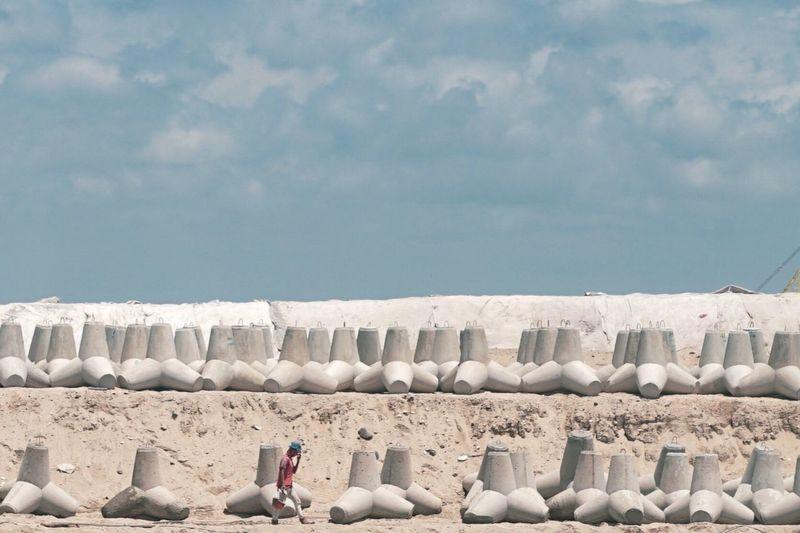 Full frame shot of white stones on beach against sky