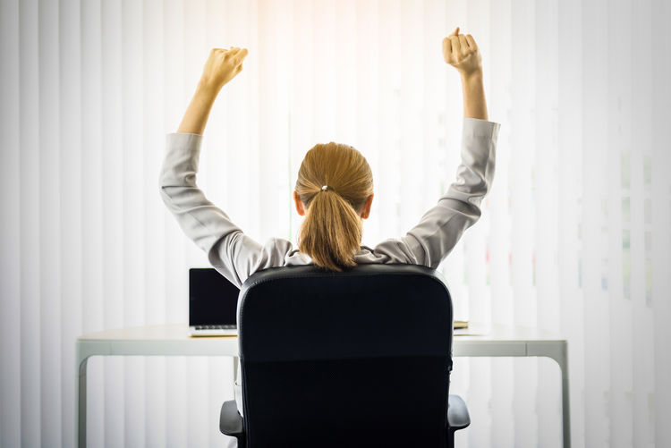Rear View Of Woman With Clenched Fists Sitting At Desk Against Blinds In Office
