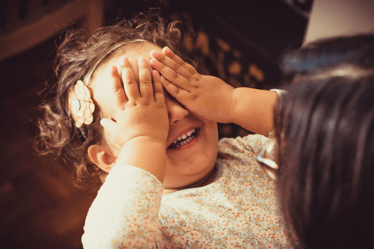 Happy small girl having fun while playing peekaboo game with her mother.