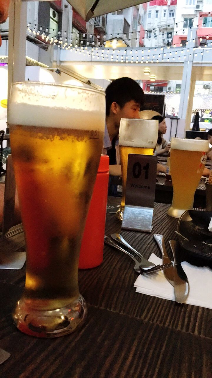 beer - alcohol, beer glass, alcohol, drink, real people, drinking glass, refreshment, beer, chair, full length, food and drink, indoors, one person, frothy drink, standing, day, freshness, people