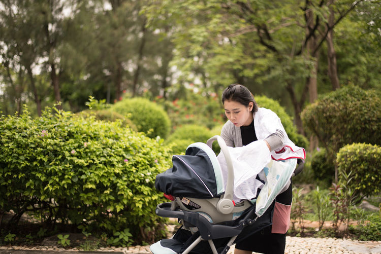 Woman arranging clothes in baby stroller while standing against plants at park