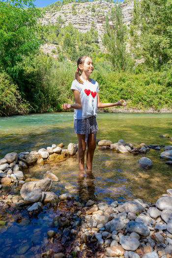 Cute girl standing by river in forest