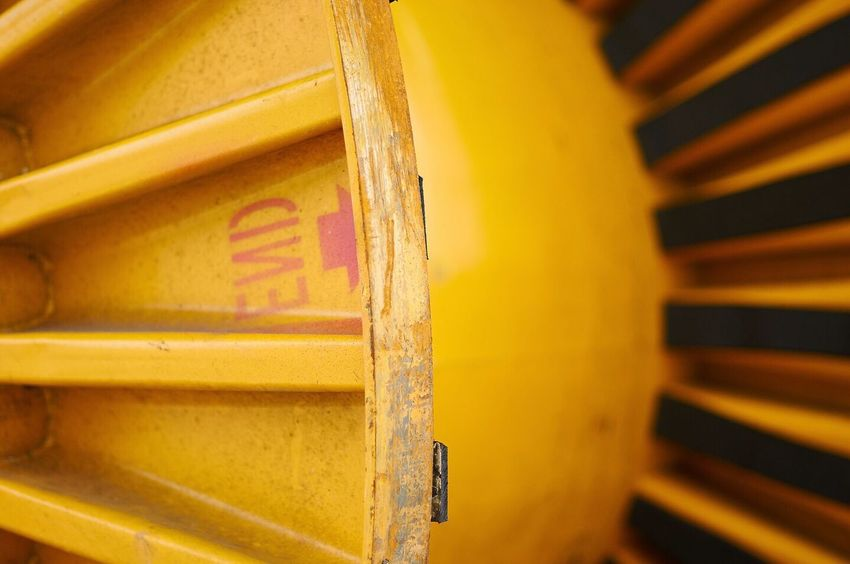 """Close up of heavy duty yellow cable drum with """"End"""" written in mirror on one segment Heavy Heavy Duty Industrial Construction Urban Yellow Colour Colour Of Life Pivotal Ideas End Finality Message Pastel Paint The Town Yellow"""