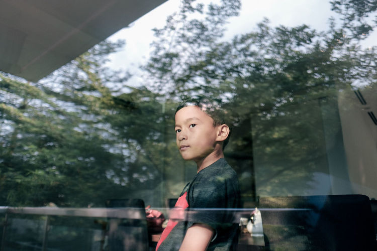Portrait of boy looking away while standing by railing against trees