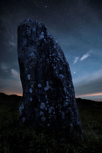 Rock formation on field against sky at night
