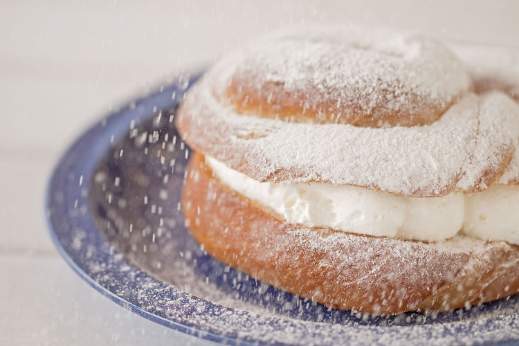 Cream puff filled with wipped sugar falling.