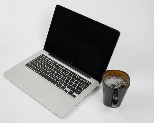 High angle view of coffee and laptop on table