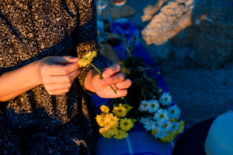 Close-up of woman holding flower outdoors