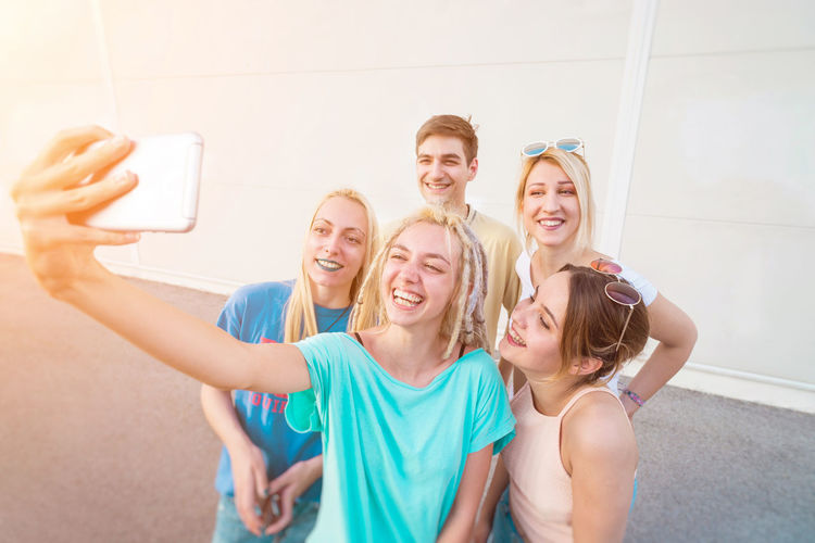 Smiling friends taking selfie through mobile phone