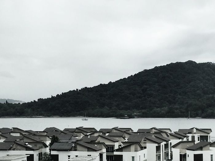 Houses by sea against mountain
