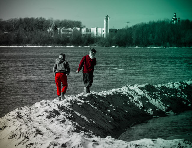 Rear view of man and woman standing in lake
