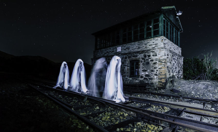 Group Of Ghosts Walking On Railroad Track At Night