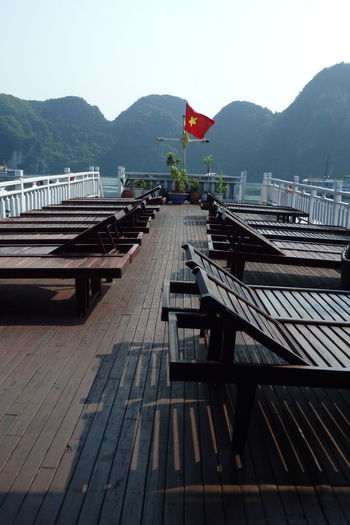 Lounge chairs on pier by mountains