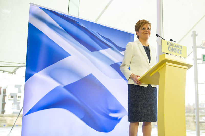Low angle view of woman standing against blue wall