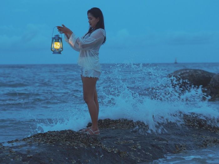 Side view of young woman with illuminated oil lamp standing at beach against sky