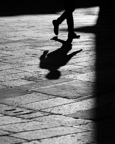 Low section of silhouette man walking on street
