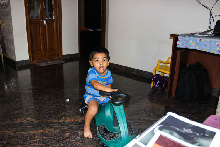 Portrait of boy sitting on toy at home