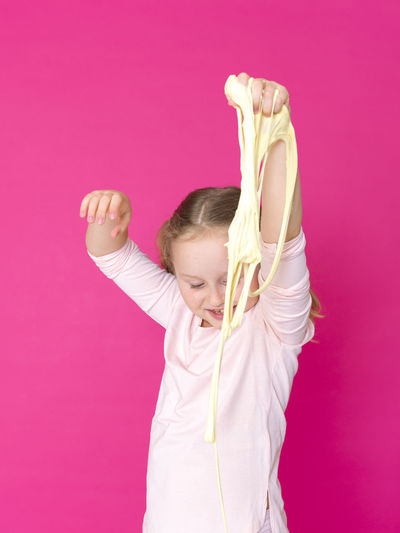 beautiful 8 year old girl is playing with yellow slime in front of pink background Slime Kid Child Playing Yellow Copy Space Girl Sticky Slimy Happy Slippery Play Girls Friends One Family Toy Funny Fun Homemade Handicraft Glue Knead Dough Colorful Inventor Science Pink Green Elementary School Child Portrait Pose Stretch Disgusting  Pull Wet Moist Shape Soft Mucus  Blond Studio 8 Years Young Cute Colored Background One Person Pink Color Indoors  Studio Shot Pink Background Human Arm Arms Raised Women Females Waist Up Childhood Lifestyles Front View Wall - Building Feature Hairstyle Innocence Hand Raised