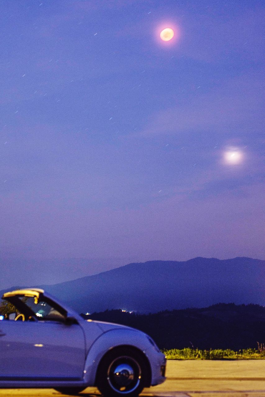 mode of transportation, car, motor vehicle, transportation, sky, land vehicle, no people, scenics - nature, nature, beauty in nature, mountain, landscape, environment, night, moon, travel, road, outdoors, illuminated, field, road trip, wheel, moonlight