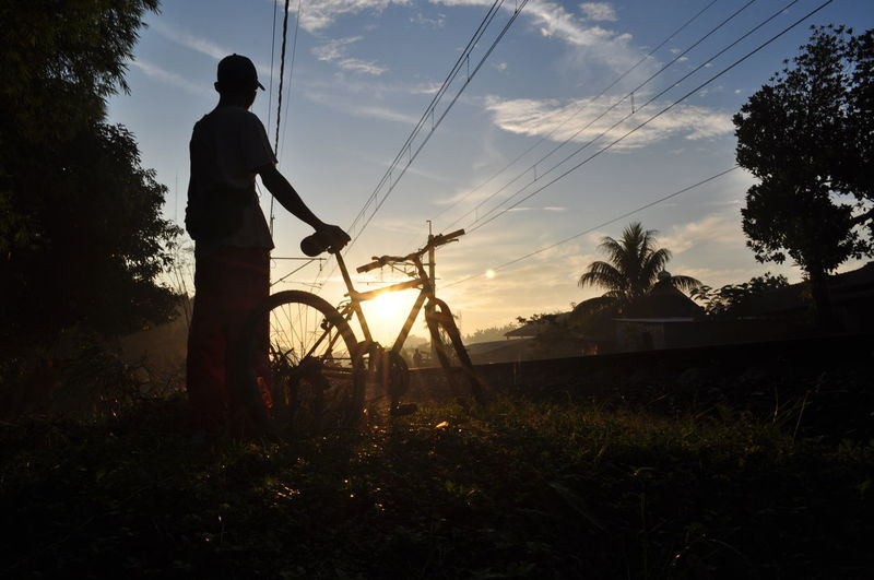 Rear View Of Man With Bicycle By Railroad Track Against Sky During Sunset