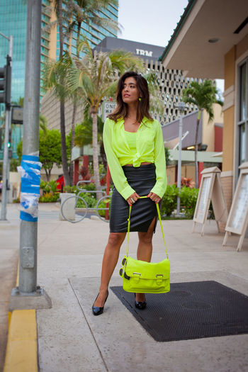 Portraits in Honolulu neon life Diverse Faces Hapa Brunette Long Hair Tied Knot Leather Skirt  Neon Holding Bag Architecture Beautiful Woman Beauty Building Exterior Built Structure Casual Clothing Day Front View Full Length Leisure Activity Lifestyles Looking At Camera Neon Yellow One Person Outdoors People Portrait Real People Tree Young Adult Young Women