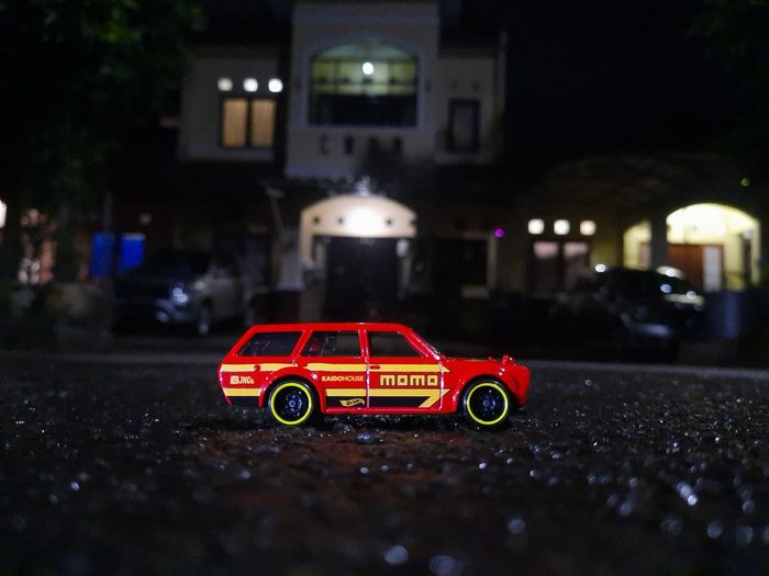 Red toy car on road at night