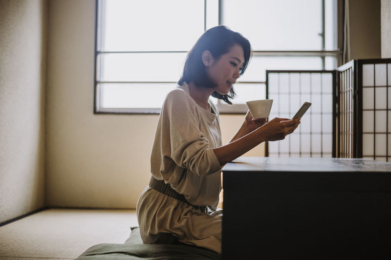 Woman drinking coffee while using smart phone sitting by table at home