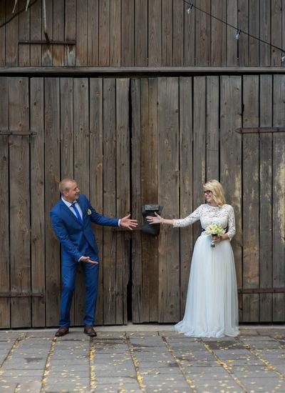 Smiling bridal couple gesturing standing against door of barn
