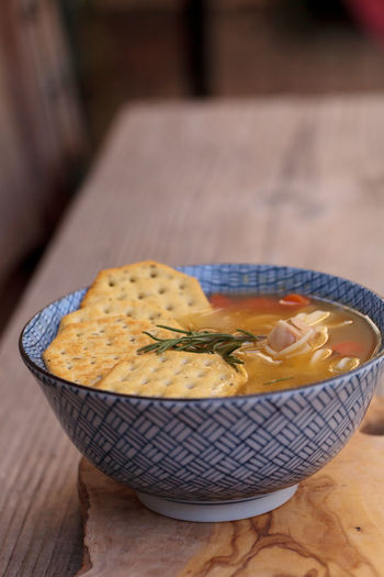 Close-up of soup with crackers on wooden table