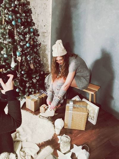 Full length of young woman wearing ice skate by christmas tree