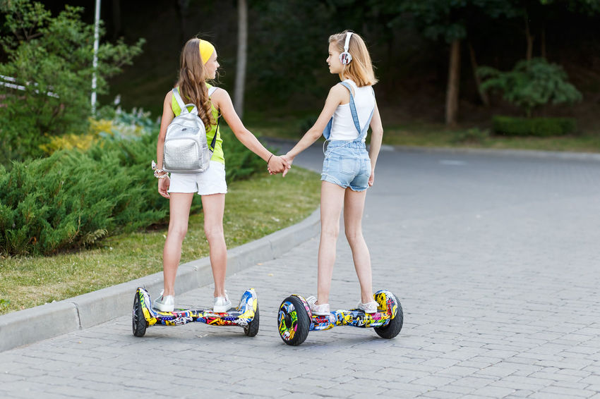 Happy girls riding on hover boards or gyroscooters outdoors at sunset in summer. Active life concept Fountain Active Board Concept Day Friendship Gadget Gyroboard Gyrometer Hovering Hovering Birds Lifestyles Outdoors Real People Sunset Two People
