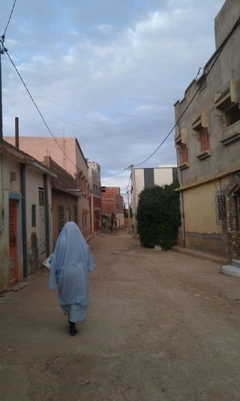 alone beautiful woman walking on the road Beautiful Woman Houses Road Alone EyeEm Selects Loneliness Moroccan Style Woman Portrait Woman Who Inspire You Roadside Traditional Alone Thinking Full Length City Rear View Walking House Sky Architecture Building Exterior Cloud - Sky Town Human Back Back Housing Settlement