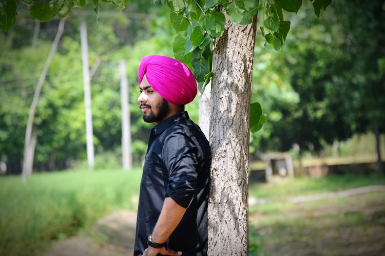 Side view of man wearing turban by tree on field
