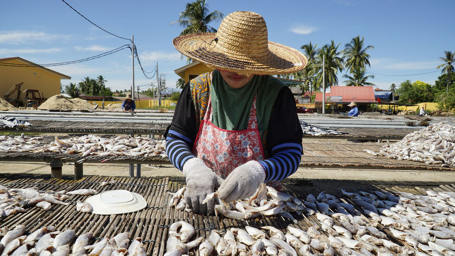 Woman selling fishes at market against sky