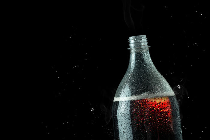 Soft drink bottle with ice splash on dark background. Soft drink bottle in celebration party concept. Container Studio Shot Refreshment Bottle Drink Black Background Alcohol Indoors  Food And Drink Close-up No People Glass - Material Copy Space Single Object Still Life Freshness Water Glass Wine Impact Blob Softdrink Softdrinks Bottles Cola