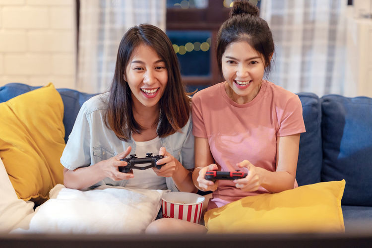 Happy young women playing video game while sitting on sofa at home