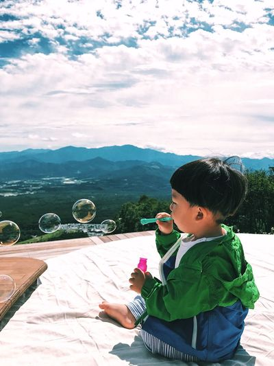 Boy playing with bubble wand while sitting on mountain against sky
