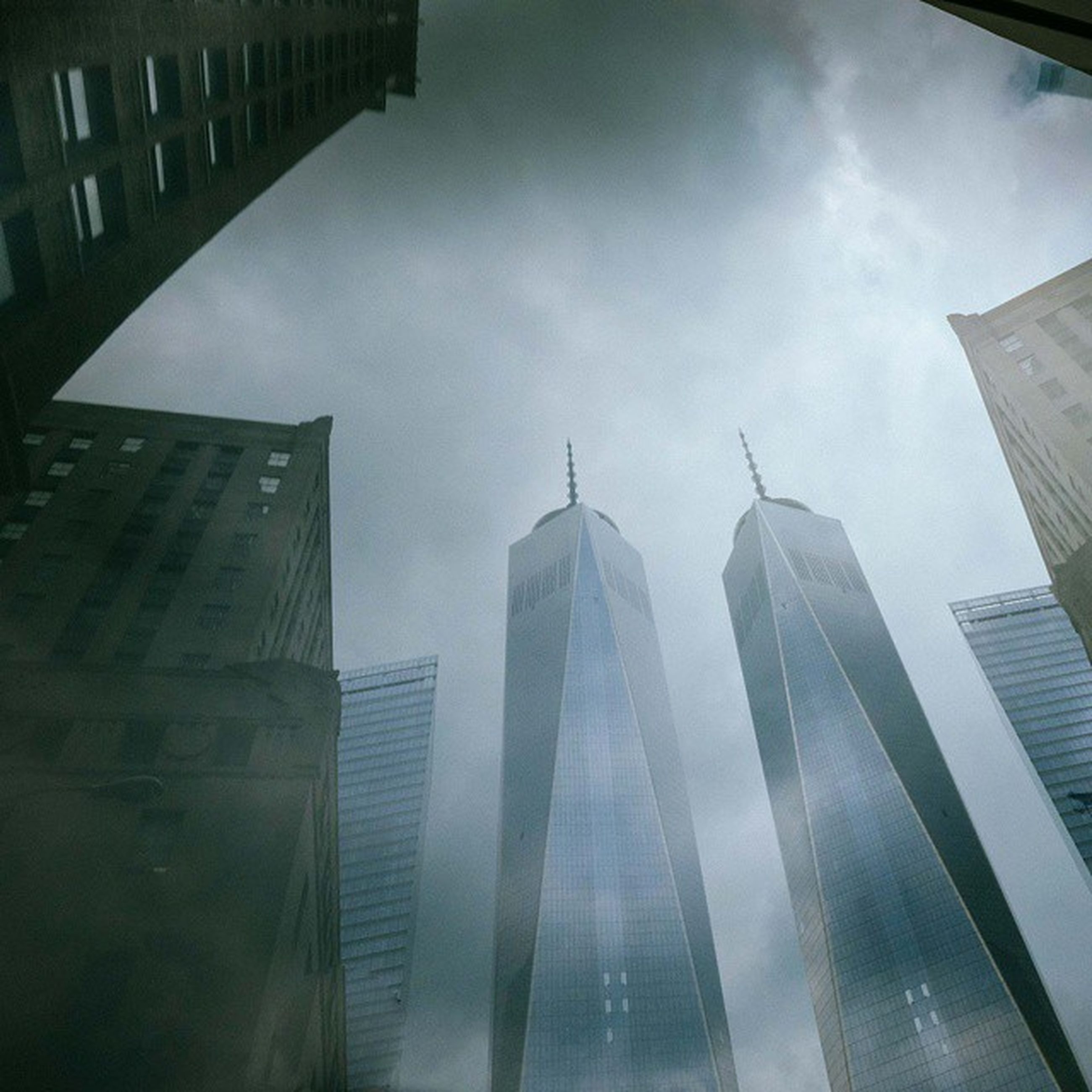 architecture, building exterior, built structure, skyscraper, city, modern, tall - high, office building, tower, sky, low angle view, capital cities, cloud - sky, glass - material, financial district, reflection, travel destinations, building, tall, city life