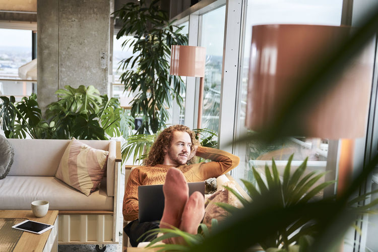 Portrait of young woman sitting on sofa in potted plant