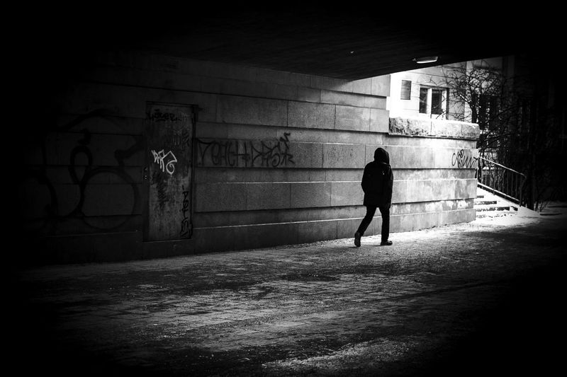 Rear view of silhouette man walking on alley amidst buildings in city