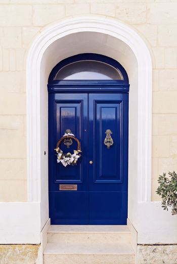 Beautiful wooden blue door decorated with Christmas wreath Christmas Christmas Wreath Decor Malta Traditional Culture Arch Architecture Blue Blue Sky Building Exterior Built Structure Closed Day Door Knocker Minimalism No People Outdoors Postbox