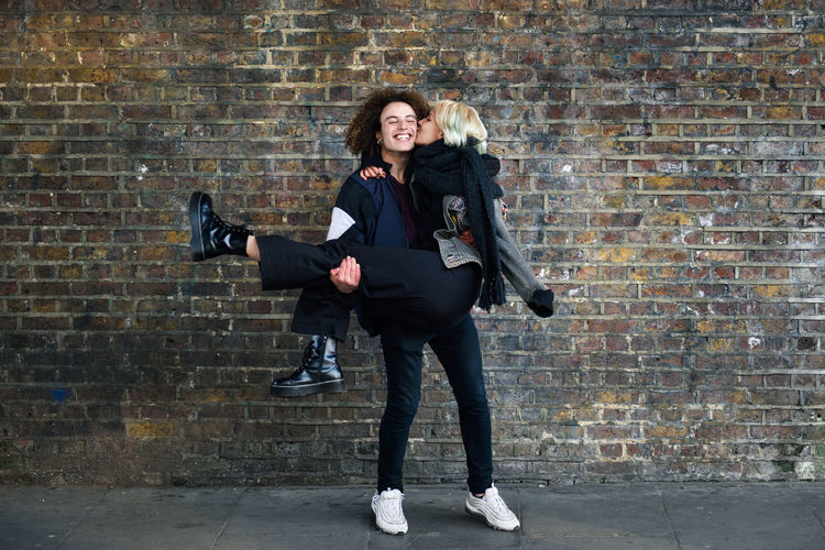 Woman kissing man on cheek in city