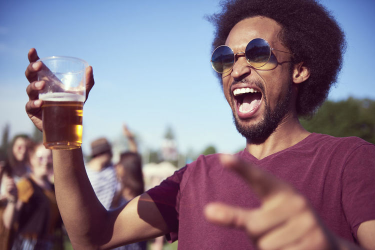 Young man screaming while enjoying beer during sunny day