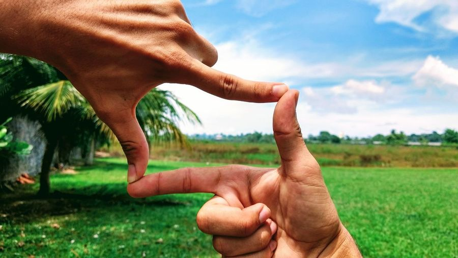 Cropped hands of people making finger frame over field against sky