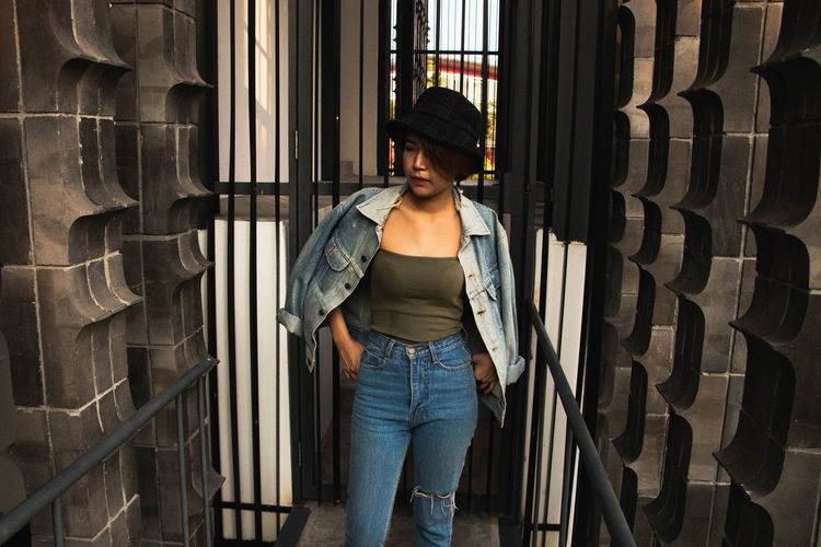 Young woman looking away standing against metal entrance
